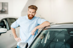 Bearded young man standing with new car in auto salon Stock Image