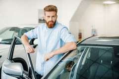 Bearded young man standing with new car in auto salon Royalty Free Stock Photos