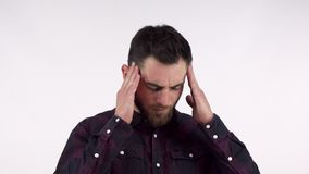 Bearded young man suffering from terrible headache, rubbing his temples. Man having painful migraine, posing isolated with his hands to his head. Remedy stock footage