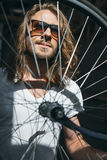 Bearded young man in sunglasses posing with bicycle wheel Stock Image