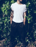 Bearded young man with tattoo wearing blank white tshirt and black sunglasses.Green garden wall background. Vertical Stock Photo