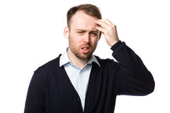 Bearded young man with a throbbing headache. Frowning as he grimaces in pain and holds his hand to his throbbing head, on white Royalty Free Stock Photo