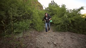 Young man is traveling with backpack in mountains. Bearded young man is traveling with a large backpack in the mountains. Attractive hiker with big traveling stock footage