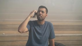 Young man in t shirt having emotional phone talk outside. Bearded young man wearing blue t shirt sitting on stairs outside and talking on the phone emotionally stock footage