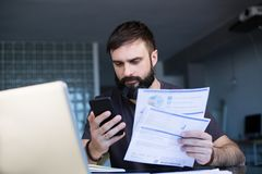Bearded young man working with laptop at home browsing bills and documents . Businessman going through paperwork at home. Office royalty free stock photography