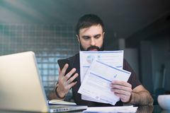 Bearded young man working with laptop at home browsing bills and documents . Businessman going through paperwork at home. Office royalty free stock photos