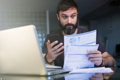 Bearded young man working with laptop at home browsing documents . Businessman going through paperwork at home office. With unpaind bills royalty free stock image