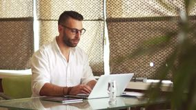 Bearded young man working in office, laptop, carefully looking through glasses, smiling. Freelancer, roman blinds stock footage