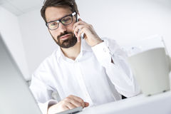 Bearded young manager on his phone at work Royalty Free Stock Image