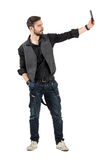 Bearded young trendy hipster guy taking selfie profile view Stock Image