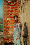 Bearded zombie man. With beard young vampire or bloody war soldier with wounds and red blood outdoors on brick wall Royalty Free Stock Photography