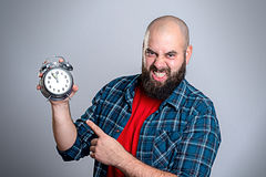 Beardet man pointing to a clock Stock Images
