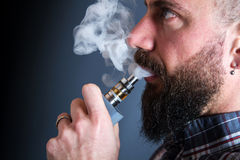 Beared man  smoking electronic cigarette Stock Images