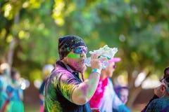 Beareded人喷溅与在颜色乐趣奔跑的粉末饮用水 库存图片