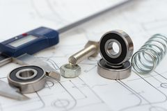 Bearing and caliper and spring and bolt with nut on mechanical engineering drawing. Bearing and caliper and spring and bolt with nut on a mechanical engineering royalty free stock image