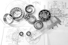 Bearings and drawings under a desk lamp. A choice of bearings by the size for assembly of a nave - according to drawings, workplace of the designer, black-and stock photos