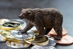 Bearish market concept, price down or falling demand collapse of. Crypto currency, bear figure standing on various of cryptocurrency physical coins, Bitcoin stock photography