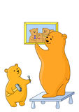 Bears attach a picture. Teddy-bears: father and the son attach a picture on a wall Royalty Free Stock Photography