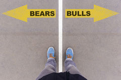 Bears vs Bulls text arrows on asphalt ground, feet and shoes on stock photos