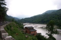 Beas Valley 3. Himachal Pradesh, India, the Beas River, the Mountanous Highway, a field and a house Stock Photography