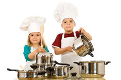 The beat of culinary art. Two kids dressed as chefs making noise with the pots and wooden spoons - isolated Stock Images