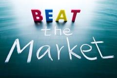 Beat the market. Conceptual words on blackboard stock photo