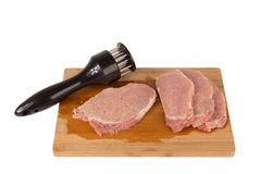 Beat the meat on a wooden board on a white background. Beat the meat and make it soft on a wooden board on a white background Royalty Free Stock Images