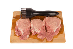 Beat the meat on a wooden board on a white background. Beat the meat and make it soft on a wooden board on a white background Stock Photo