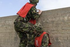 Beat the wall. 2 UK soldiers use teamwork to get over a wall royalty free stock photo