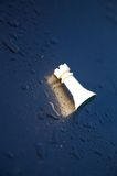 Beaten Castle chess piece. Castle chess piece on wet surface royalty free stock images