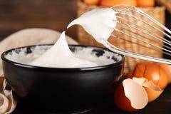 Beaten egg whites. And a whisk royalty free stock photos