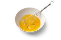 Beaten egg yolks in a bowl with whisk. On white background royalty free stock image