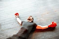 Beaten man on the boxing ring. Beaten man lying on the floor of the boxing ring during the knockout royalty free stock image