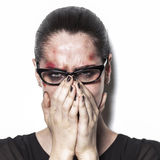 Beaten up girl crying and covering mouth with hands Royalty Free Stock Image