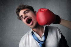 Beaten. Young businessman punched by a boxing glove stock photography