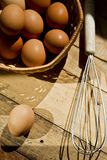 Beater and baskets of eggs on wooden background stock photo