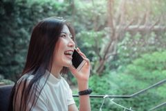 Beatiful asian girl`s holding mobile and have emotion happy looking at mobile phone.  royalty free stock photo