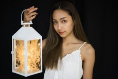 Woman hold fancy lamp on black background. Beatiful Asian woman hold fancy light bulb lamp with black background and copy space for text. Girl in scary mystery Stock Photo