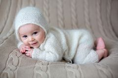 Beatiful baby boy in white knitted cloths and hat, looking curio. Usly posed in bed Royalty Free Stock Photography
