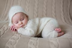 Beatiful baby boy in white knitted cloths and hat, sleeping. Sweetly posed in bed stock photo