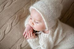 Beatiful baby boy in white knitted cloths and hat, sleeping. Sweetly posed in bed Stock Photography