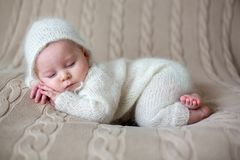 Beatiful baby boy in white knitted cloths and hat, sleeping. Sweetly posed in bed Royalty Free Stock Photography