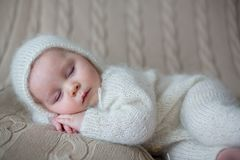 Beatiful baby boy in white knitted cloths and hat, sleeping. Sweetly posed in bed Royalty Free Stock Images