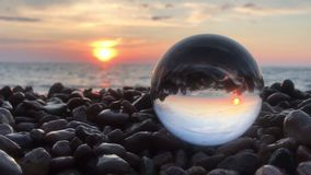 Beatiful background landscape inside crystal ball lay on beach stones, sunset and ocean waves inside stock video footage
