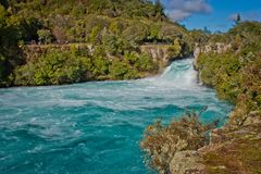 Beatiful blue water beneath of Huka Falls in Taupo in New Zealand. Perfect water for rafting, adventure tourism of New Zealand, powerfull waterfall royalty free stock image