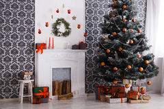Beatiful christmas decorated tree in modern interior, holiday concept. Beautiful holdiay decorated room with Christmas tree and fireplace. Winter holiday design Stock Image