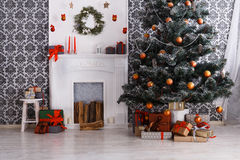 Beatiful christmas decorated tree in modern interior, holiday concept. Beautiful decorated room with Christmas tree and fireplace. Winter holiday design and Royalty Free Stock Image