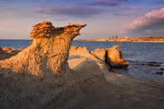 Beatiful Cyprus sunset on the desert empty rocky coast with strange fiqures at the Halk beach. Evening landscape in purple and orange at the Mediterranean sea of royalty free stock photo