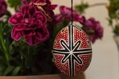 A beatiful easter egg near a flower stock photos