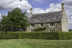 Beatiful English Country House. This idyllic country house is typical of rural England. The scene is further typified by the creeper on the facade; a single tree Royalty Free Stock Images